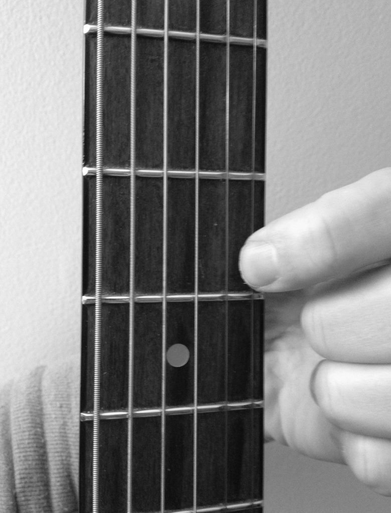 how to press down a string on a guitar